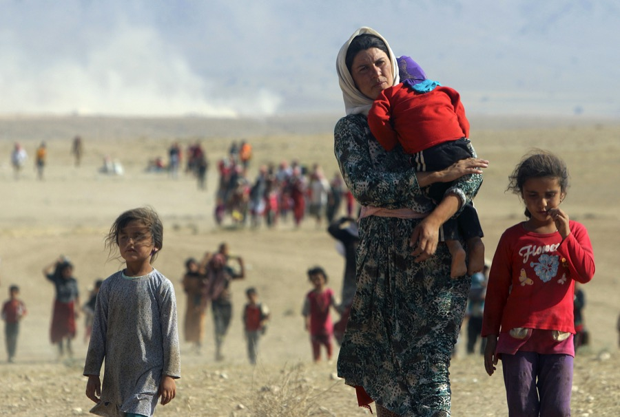 Displaced Yazidi people fleeing violence in Sinjar, walk toward the Syrian border on Aug. 11, 2014.